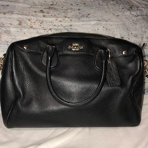 Black coach bag with gold accents and black strap